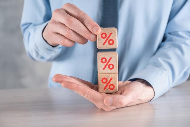 Рука бизнесмена берет деревянный кубик с изображением