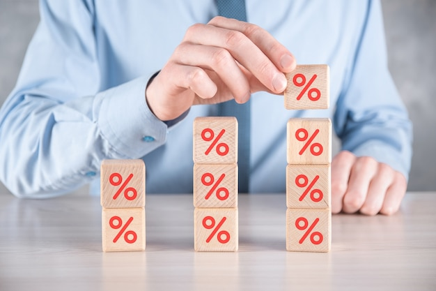 Рука бизнесмена берет деревянный кубик, показывая символ процента.
