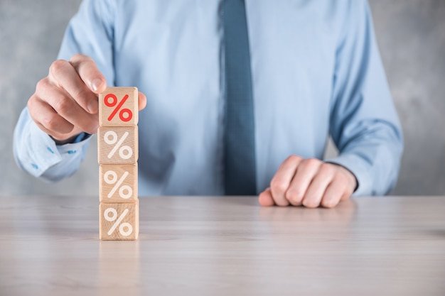 Businessman hand takes a wooden cube block depicting,shown the percentage symbol icon. interest rate financial and mortgage rates concept.