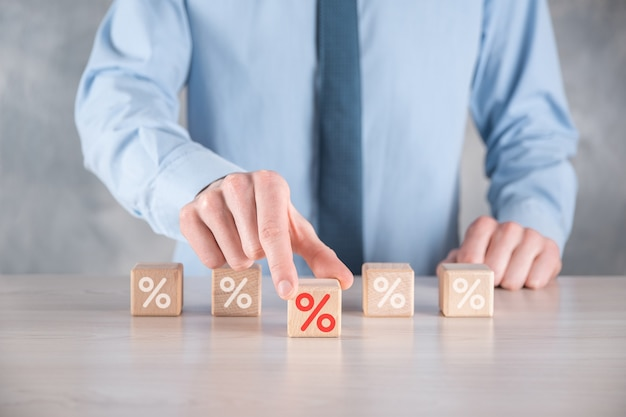 Businessman hand takes a wooden cube block depicting,shown the percentage symbol icon.
