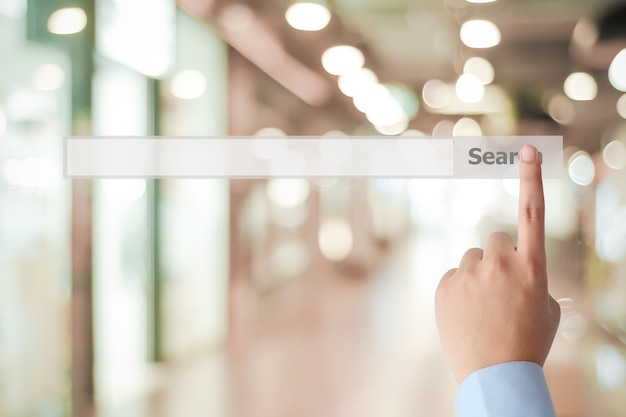 Businessman hand touching blank search bar over blur background