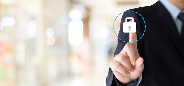 Businessman hand touching cyber security icon over blur background