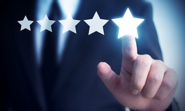 Businessman hand touching five star review to increase rating of company concept
