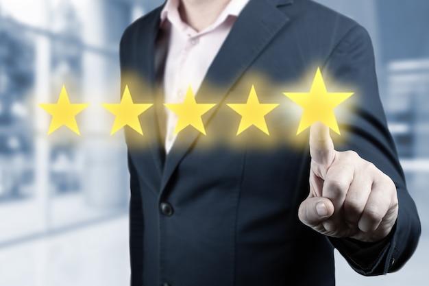5つ星のシンボルに触れるビジネスマンの手。男は五つ星を指しています-レビューと評価の概念