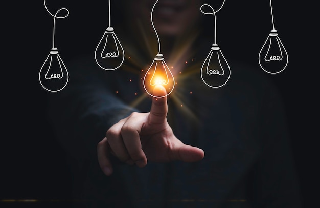 Businessman hand touching glowing lightbulb among lamp does not light for selective creative smart thinking ideas and innovation concept.