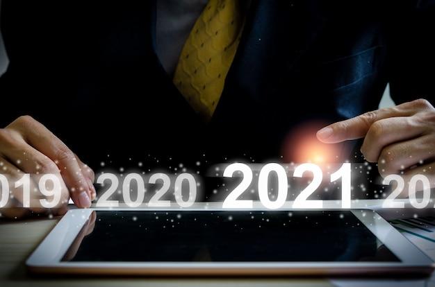 Рука бизнесмена касаясь виртуального экрана 2021 года с таблеткой на столе.