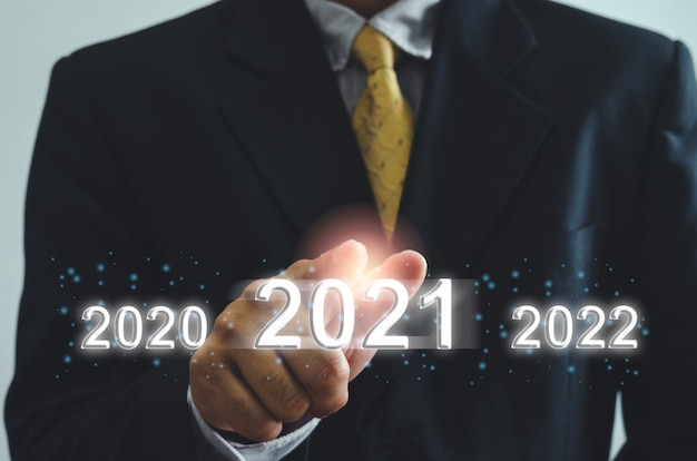Рука бизнесмена касаясь виртуального экрана 2021 года.