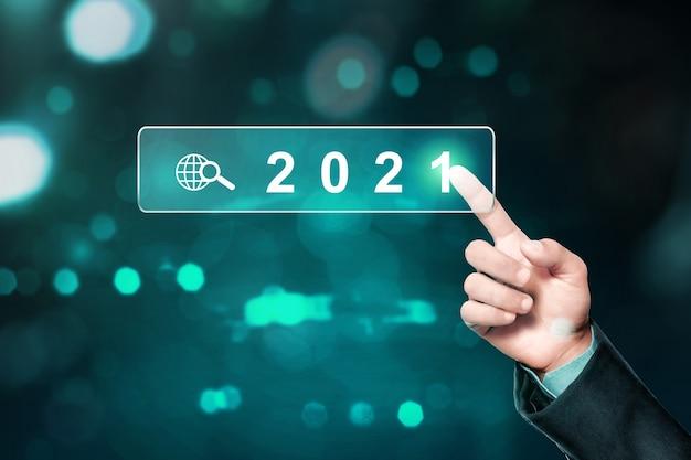 2021의 가상 화면을 만지고 사업가 손. 새해 복 많이 받으세요 2021