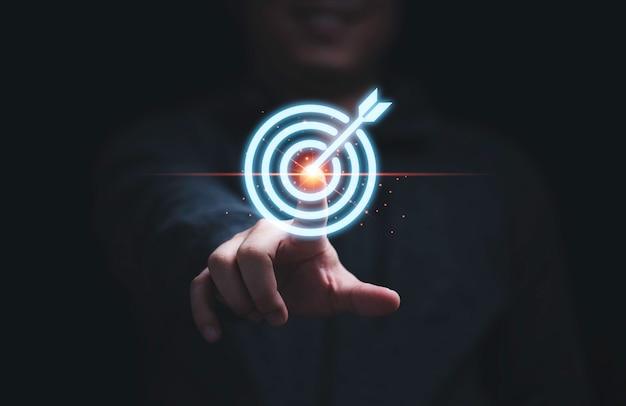 Рука бизнесмена касаясь целевой доски для дартса для установки и достижения целей цели для бизнес-инвестиционной концепции.
