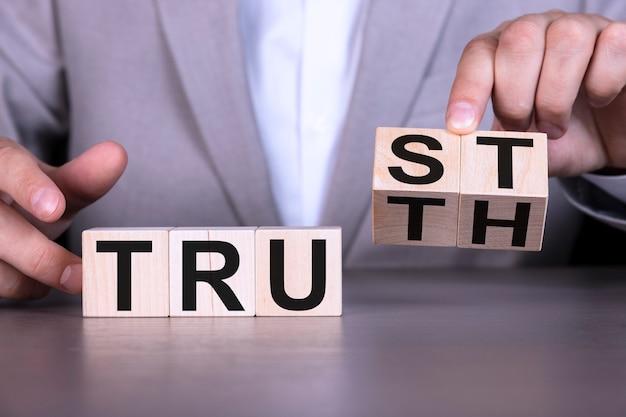 ビジネスマンの手が木製の立方体をひっくり返し、言い回しを信頼から真実に変更します