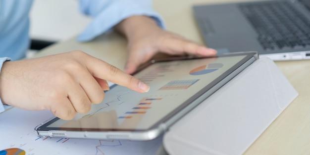 Рука бизнесмена использует цифровой планшет и открывает финансовый отчет, чтобы проверить статистику бизнеса