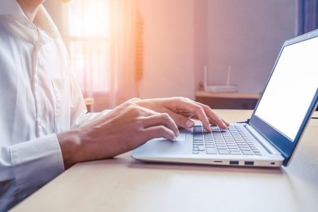 Рука бизнесмена с помощью портативного компьютера в офисе.