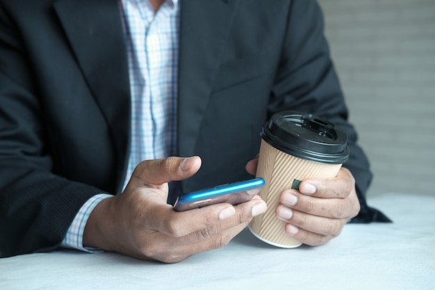Рука бизнесмена с помощью смартфона и бумажной кофейной чашки