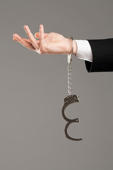 Businessman hand with opened handcuffs
