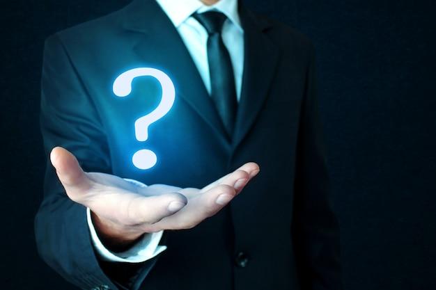 暗い青色の背景に疑問符の付いたビジネスマンの手