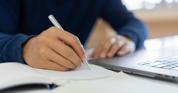 Businessman hand writing content or somethings on notebook with using laptop