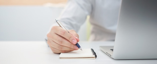 Businessman hand writing content or somethings on notebook