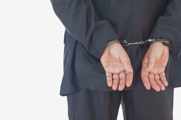 Businessman in handcuffs standing against white background