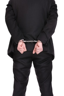 A businessman in handcuffs standing over white