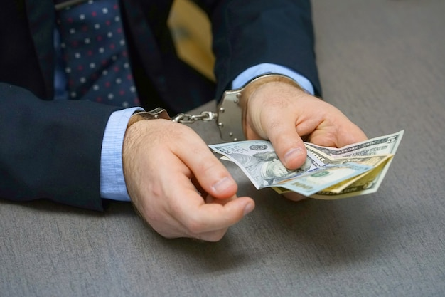 Businessman in handcuffs with a bribe