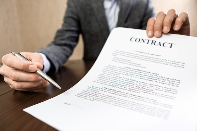 Businessman handing over a contract for signature offering a ballpoint pen in his hand