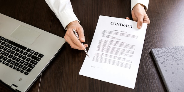 Businessman handing over a contract for signature offering a ballpoint pen in his hand.