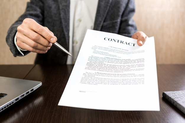 Businessman handing over a contract for signature offering a ballpoint silver pen in his hand.