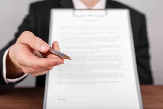 署名のためにクリップボードに添付された契約書を手渡すビジネスマンは、彼の手にボールペンを提供します。