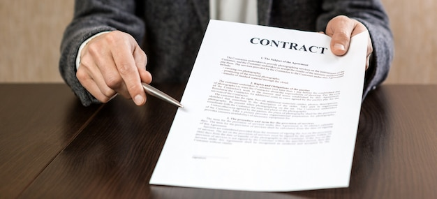 Бизнесмен передает контракт на подпись, предлагая шариковую ручку в руке