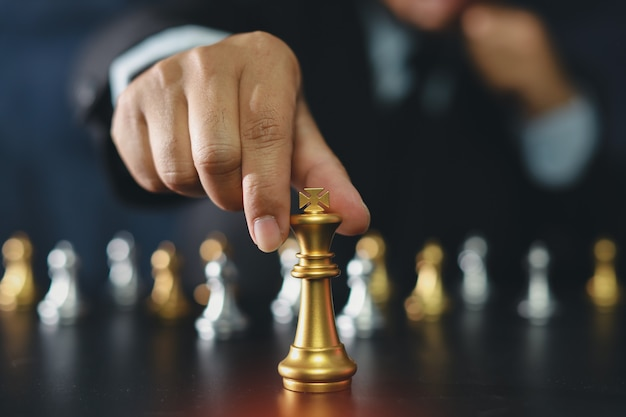 Businessman hands in black suit sitting and pointing chess king on vintage table meaning of planning and strategy