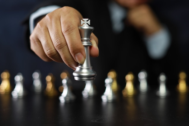 Businessman hands in black suite sitting and pointing chess king on vintage table