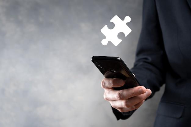 パズルのピースを接続するビジネスマンの手