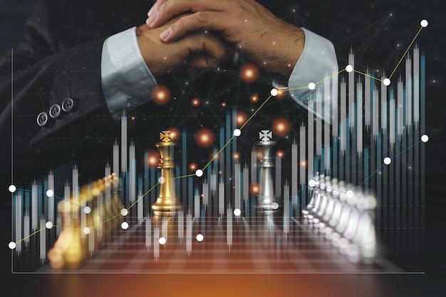 ビジネスマンの手は、未来的なグラフィックアイコンとチャート株取引でビジネス戦略と戦術のチェス盤ゲームを制御します。経営陣の競争、成功、リーダーシップのアイデア。
