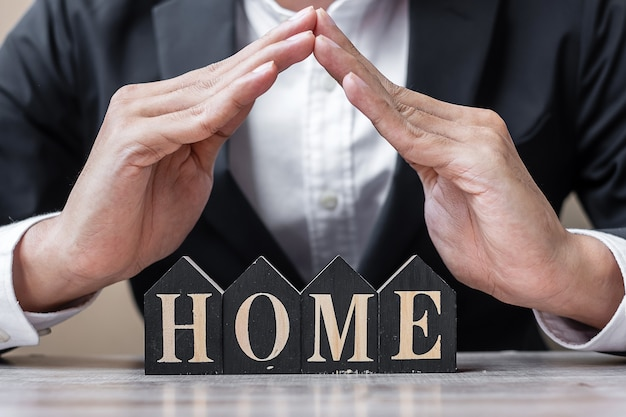Businessman hands cover wooden home model on table office.