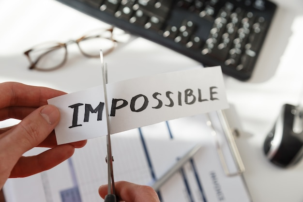 Businessman hands cutting the word impossible,