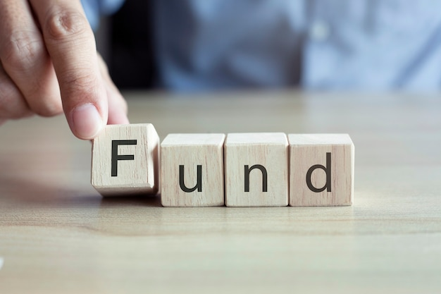 Businessman hands flips cube with fund word symbol