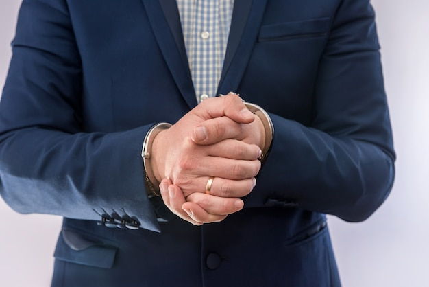 ビジネスマンの手は手錠でドルの囚人を保持します。汚職犯罪と贈収賄の概念