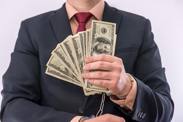 사업가 손에 수갑에 달러 포로 만요. 부패 범죄 및 뇌물 수수 개념