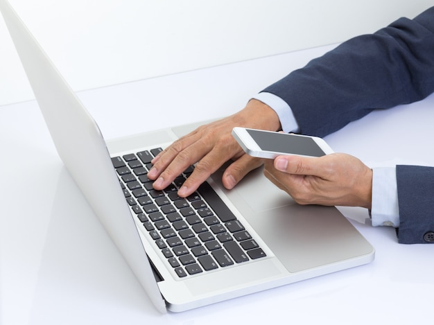 Businessman hands holding mobile phone  with laptop computer