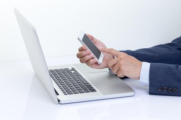 ラップトップコンピューターでスマートフォンを保持しているビジネスマンの手
