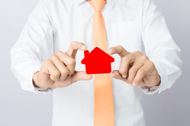 Businessman hands  holding the wooden cut house shape, isolated background