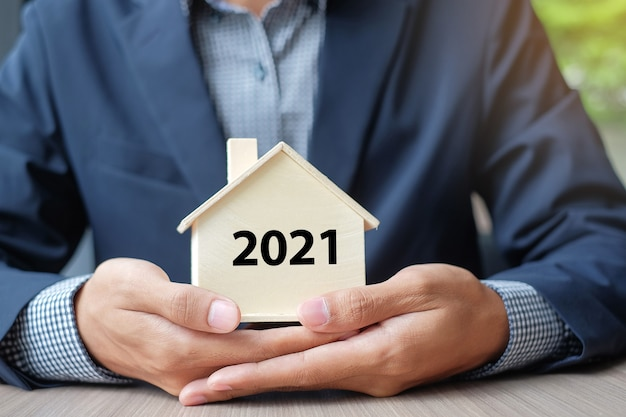 Businessman hands holding wooden house model with 2021