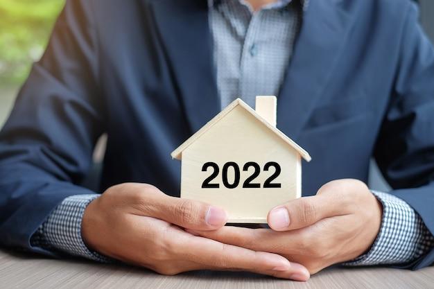사업가는 2022년 새해 텍스트가 있는 목조 주택 모델을 들고 있습니다. 재산 보험 및 부동산 개념