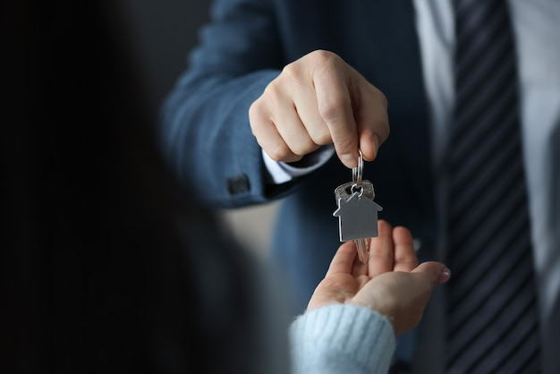 Businessman hands over house keys to client