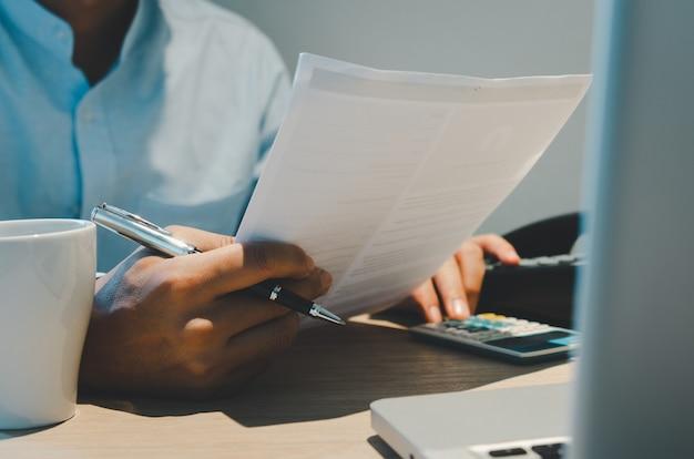 ビジネスマンは、ペンやビジネス文書を持って、コーヒーマグとコンピューターを持って机の上に手を置きます。ビジネス、金融、投資、税金のオンライン支払い