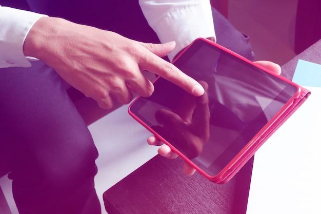 Руки бизнесмена, нажимающие на планшет