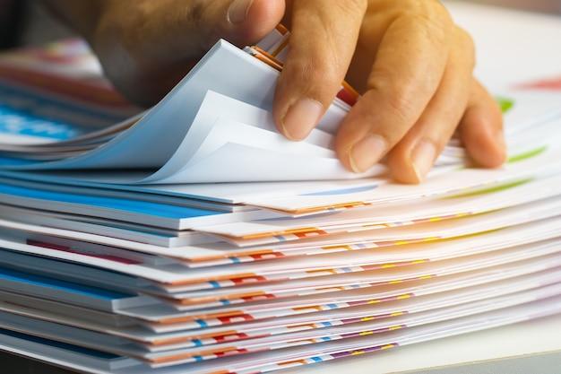 未完成の文書を探しているビジネスマンの手紙の文書をオフィスデスクに紙ファイルのスタック