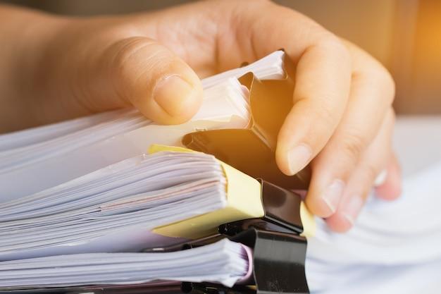未完成の文書を検索するビジネスマンの手紙ファイルのスタック