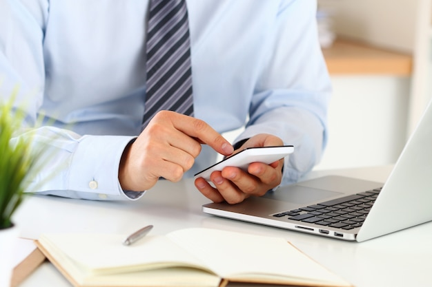 ビジネスマンの手は彼のオフィスに座っているスマートフォンで何かを入力します。クローズアップビュー