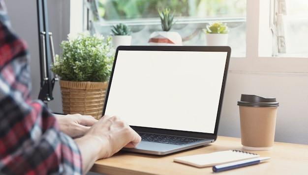 空白の画面でラップトップを使用してビジネスマンの手。コンピューターモニターのモックアップ。デザインやテキストの準備ができたコピースペース。